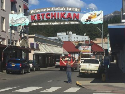 A team member under the sign for Ketchikan